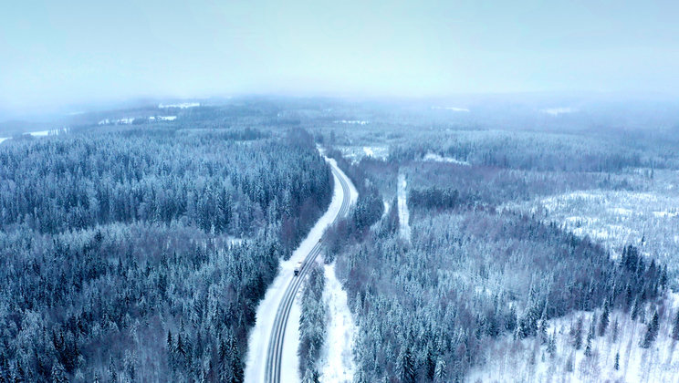 A snowy road cutting through the forest in eastern Finland